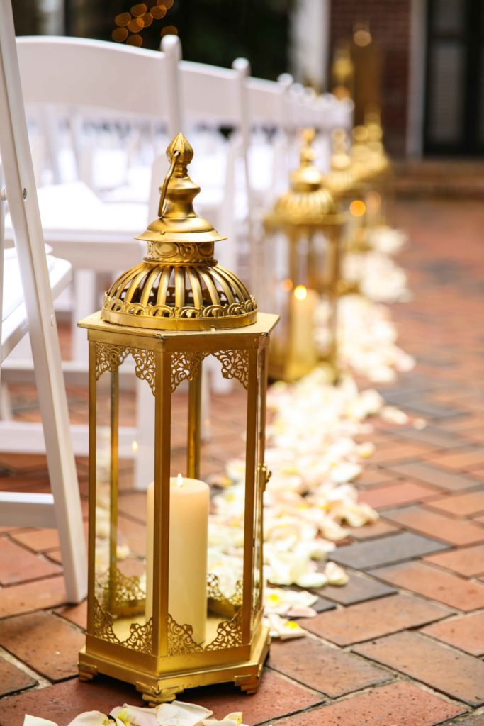 Gold lanterns line the aisle in the courtyard at Chateau LeMoyne.