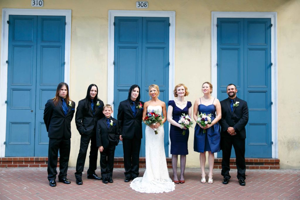 The bridal party in black and dark blue pose for a portrait in the French Quarter