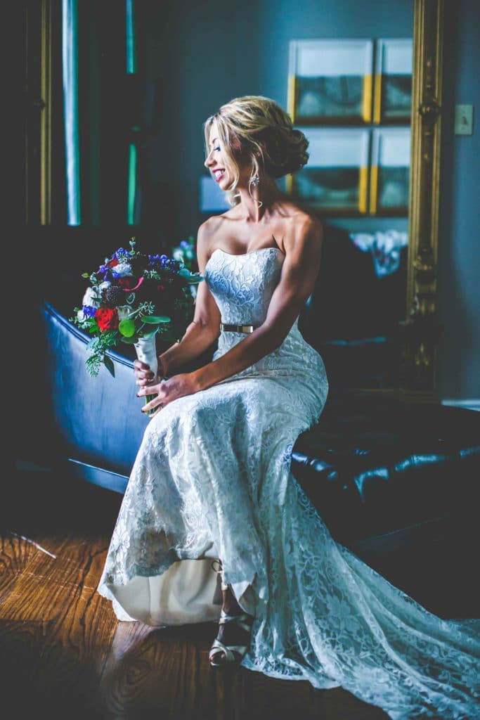 A bridal portrait of Sara by a window in her hotel room
