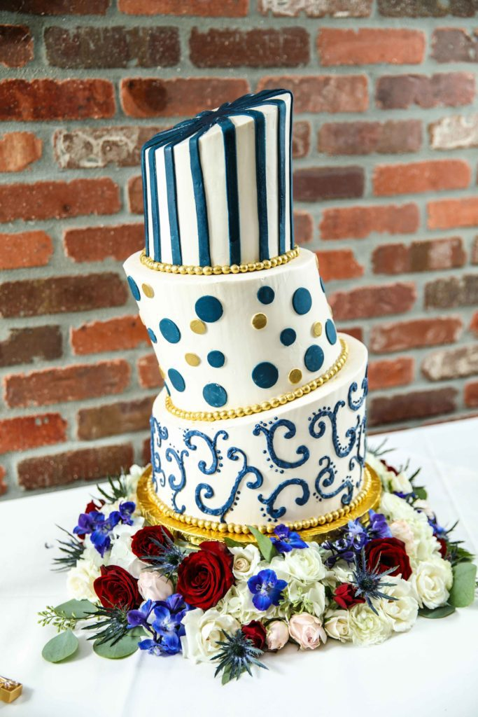 Sara's topsy-turvy wedding cake with blue and gold designs on each layer.