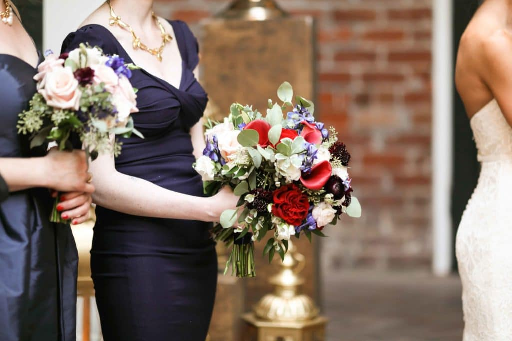The maid of honor holds Sara's bouquet during the ceremony.