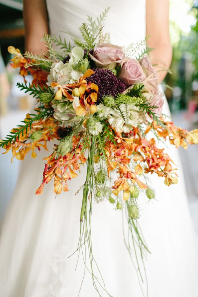 Bridal bouquet with orange orchids by Grow With Us Florist.