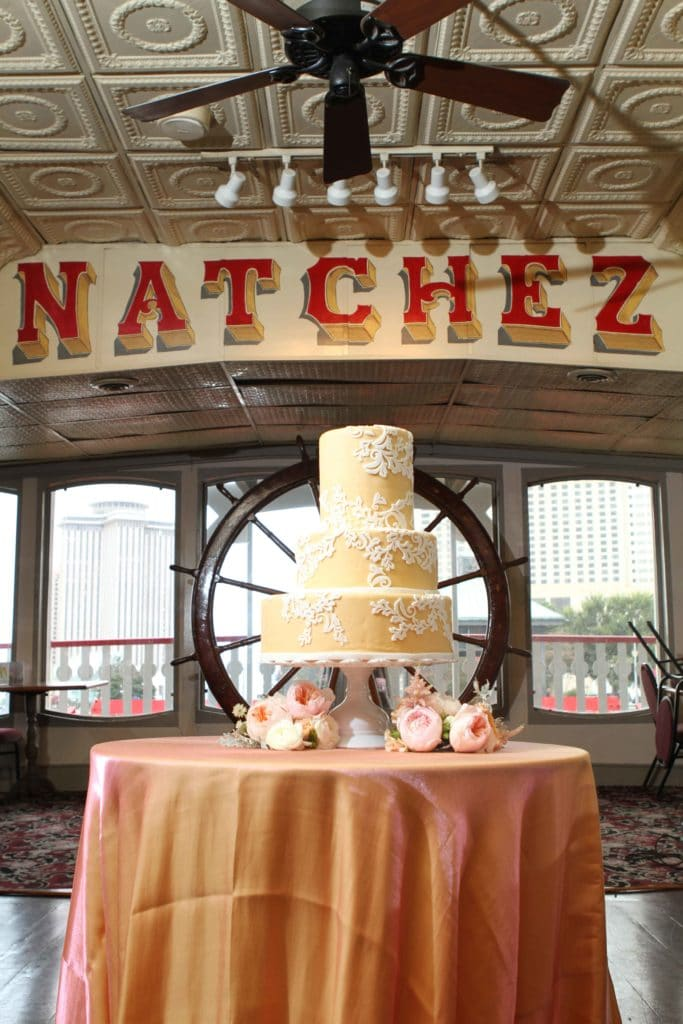 A wedding cake in front of the ship's wheel on the Steamer Natchez. Photo: Jessica The Photographer