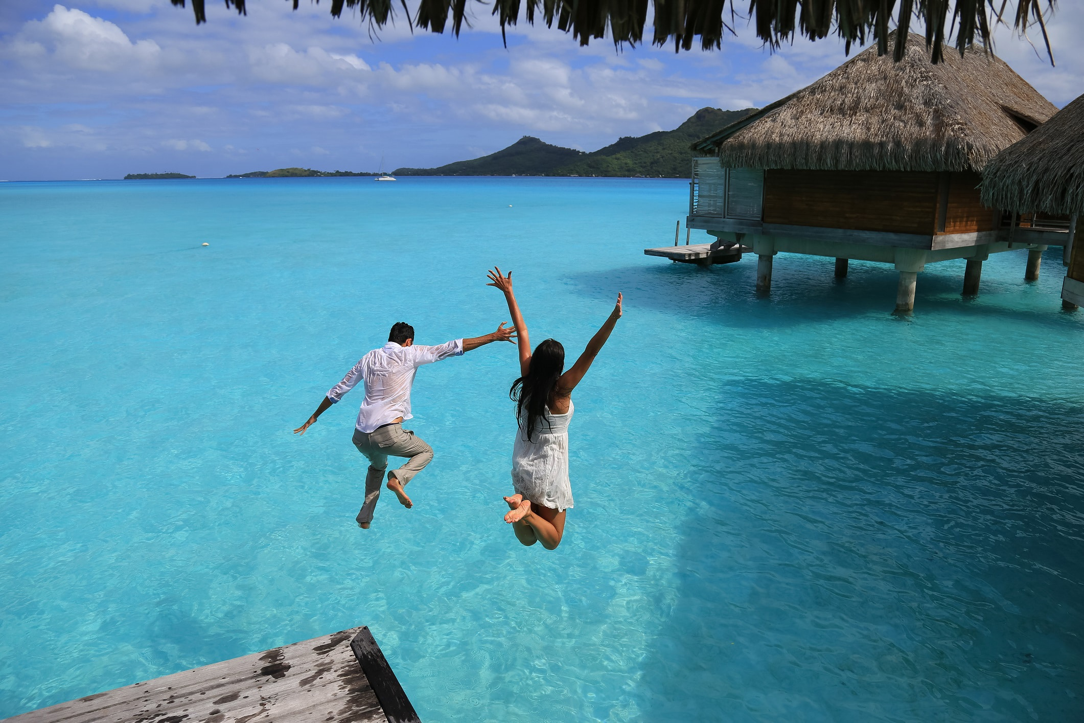 A couple jumps into water at tropical destination. Photo: Shutterstock.