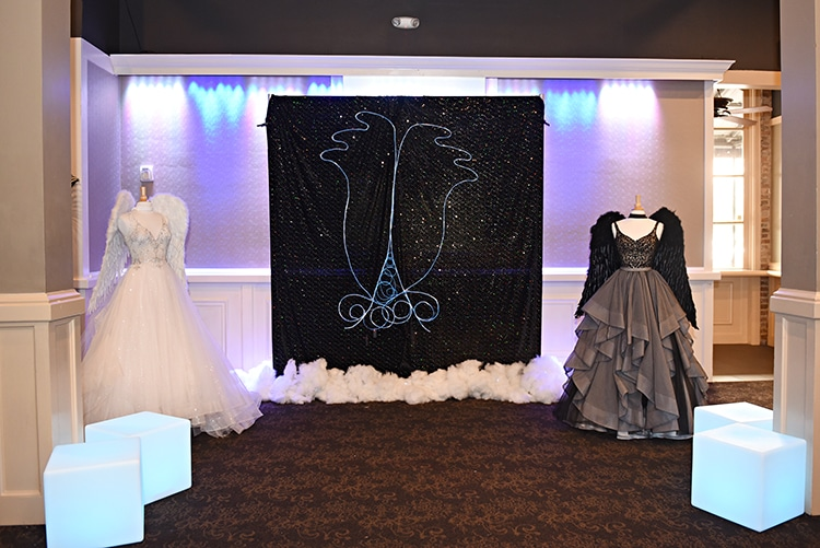 """Neon"" angel wing photo opp at the Something Blue Bridal Event in New Orleans. Lighted cube furniture by True Value Rental. Gown, left, Eve of Milady, available at Pearl's Place. Gown, right, Martina Liana Separates, available at The Bridal Boutique by MaeMe."