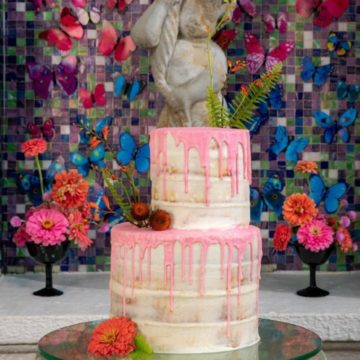 "This two-tier naked cake with watermelon pink white chocolate ""drip"" finish by Gambino's Bakery sits atop a glass base supported by a dozen miniature fish bowls. PHOTOGRAPHER: Brian Jarreau Photography"