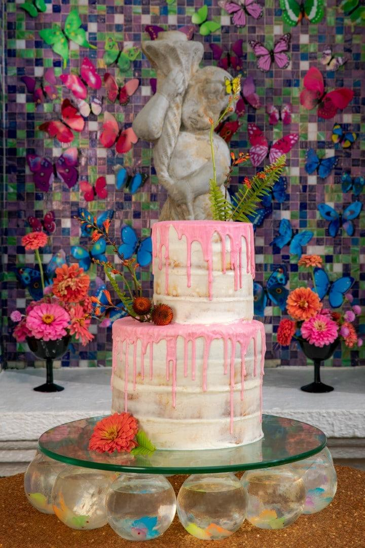 """This Two-tier Naked Cake With Watermelon Pink White Chocolate """"drip"""" Finish By Gambino's Bakery Sits Atop A Glass Base Supported By A Dozen Miniature Fish Bowls. PHOTOGRAPHER: Brian Jarreau Photography"""