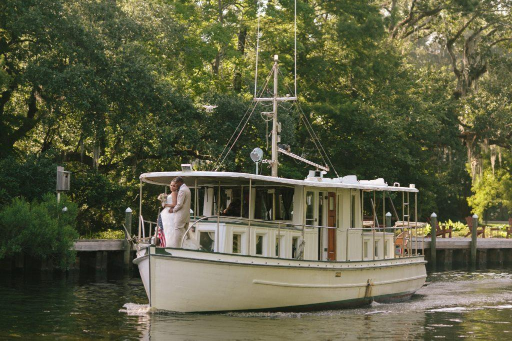 A bride and groom stand on the bow of a fishing boat on the bayou behind Palmetto's on the Bayou in Louisiana.
