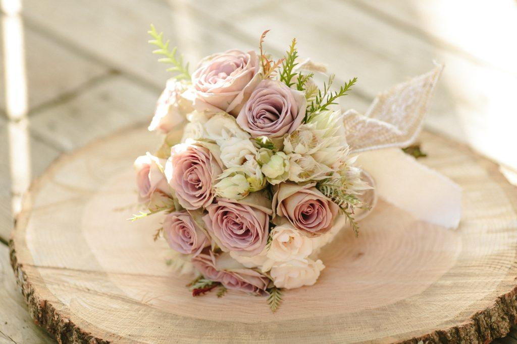 A bouquet of ivory and soft purple roses.