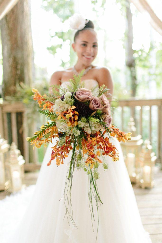 A bouquet of orange orchids with greenery and purple roses.