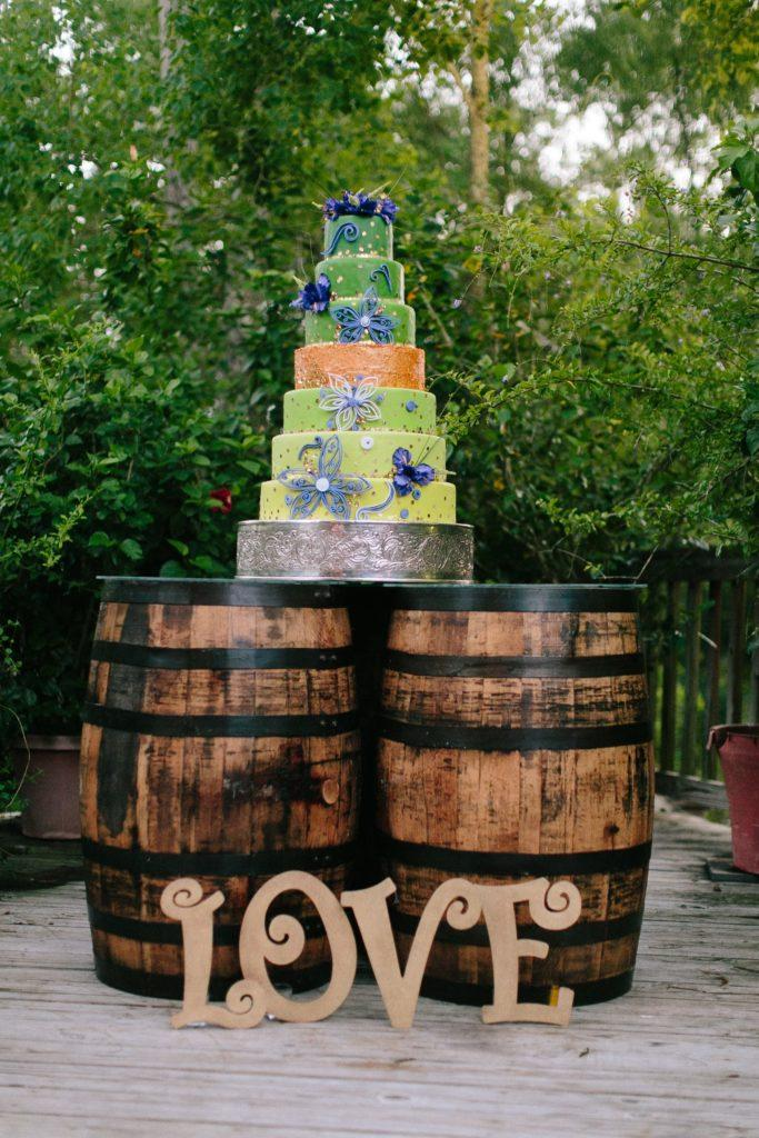 A fanciful 7-tier wedding cake sits atop a wine barrel cake table.