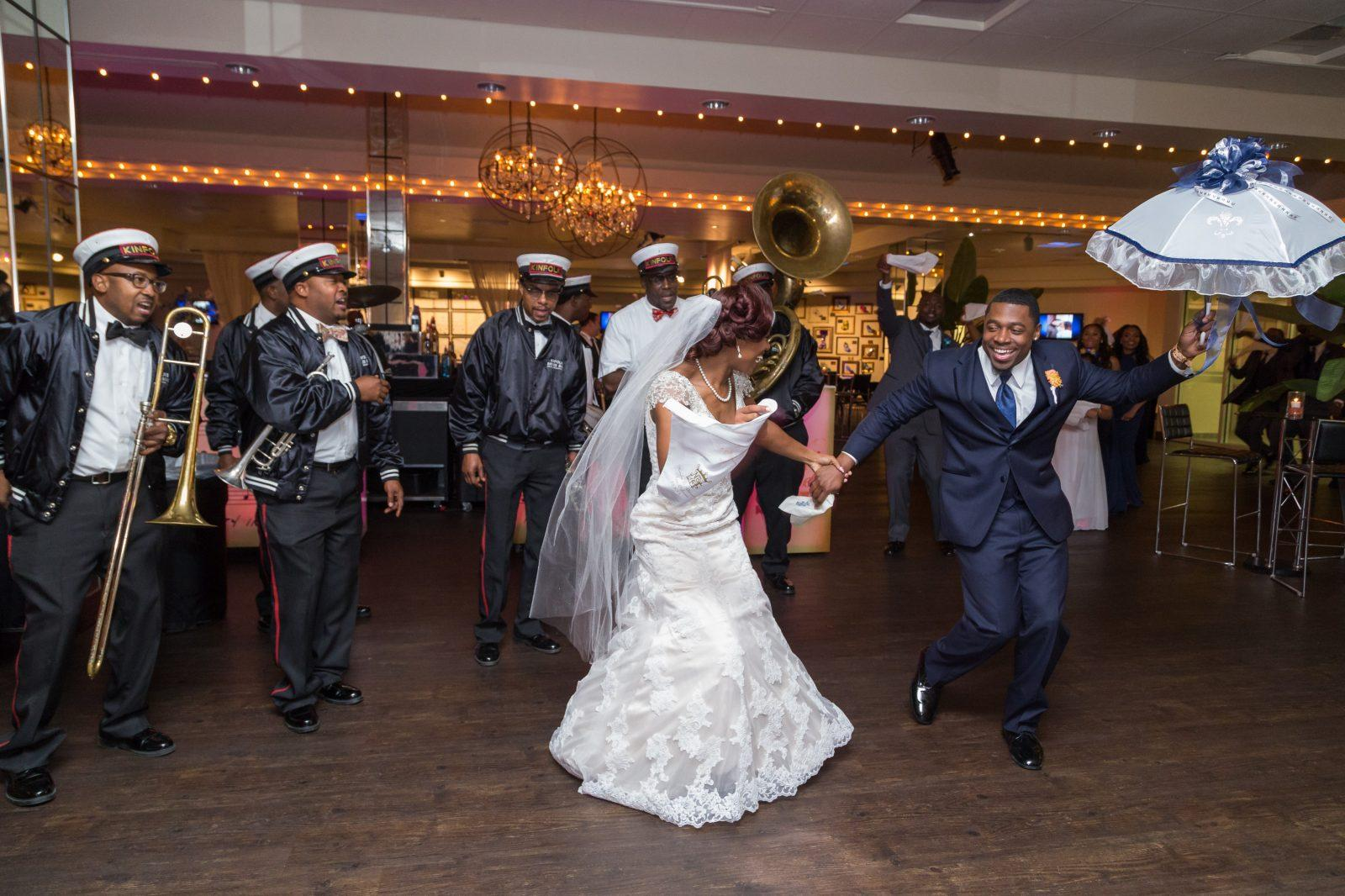 A bride and groom dance while a brass band plays. Photo: CR Photography