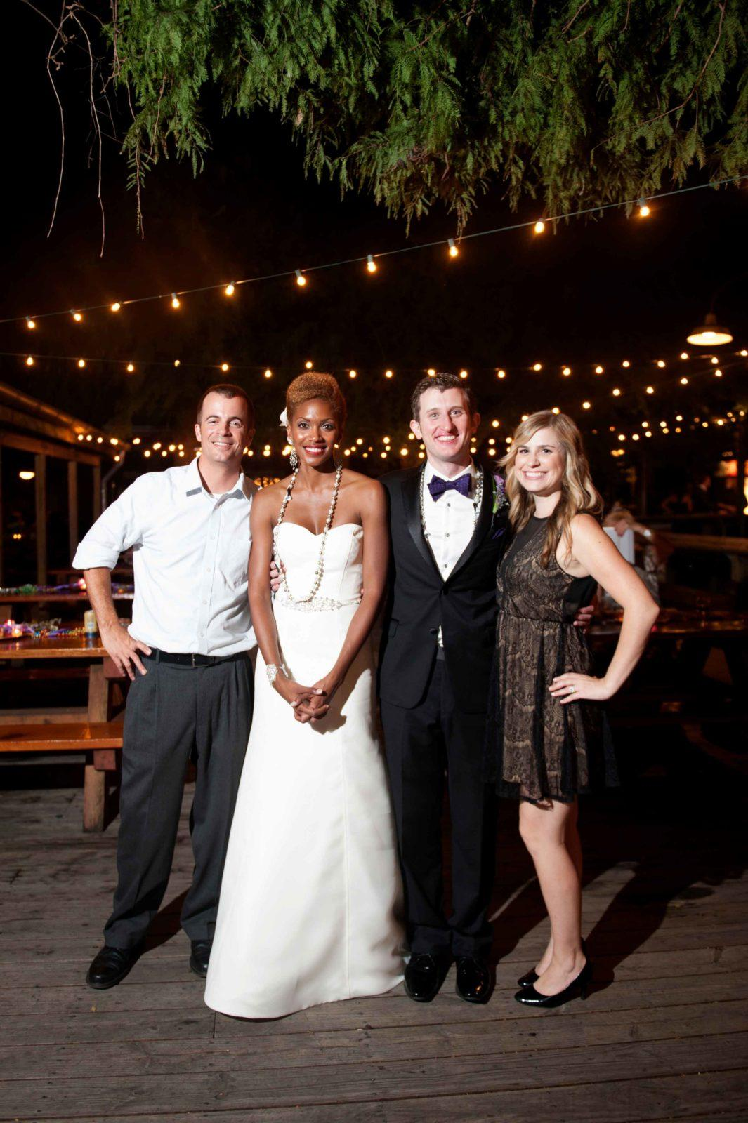 A bride and groom pose with guests outdoors at the Cajun Ballroom. Photo: Lauren Carroll Photography