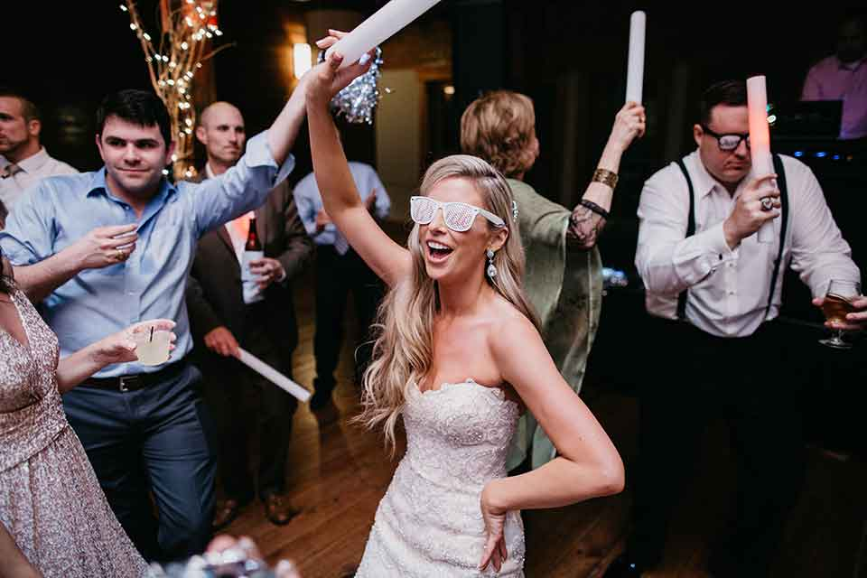 A bride and guests dance at a wedding reception. Photo: September Company