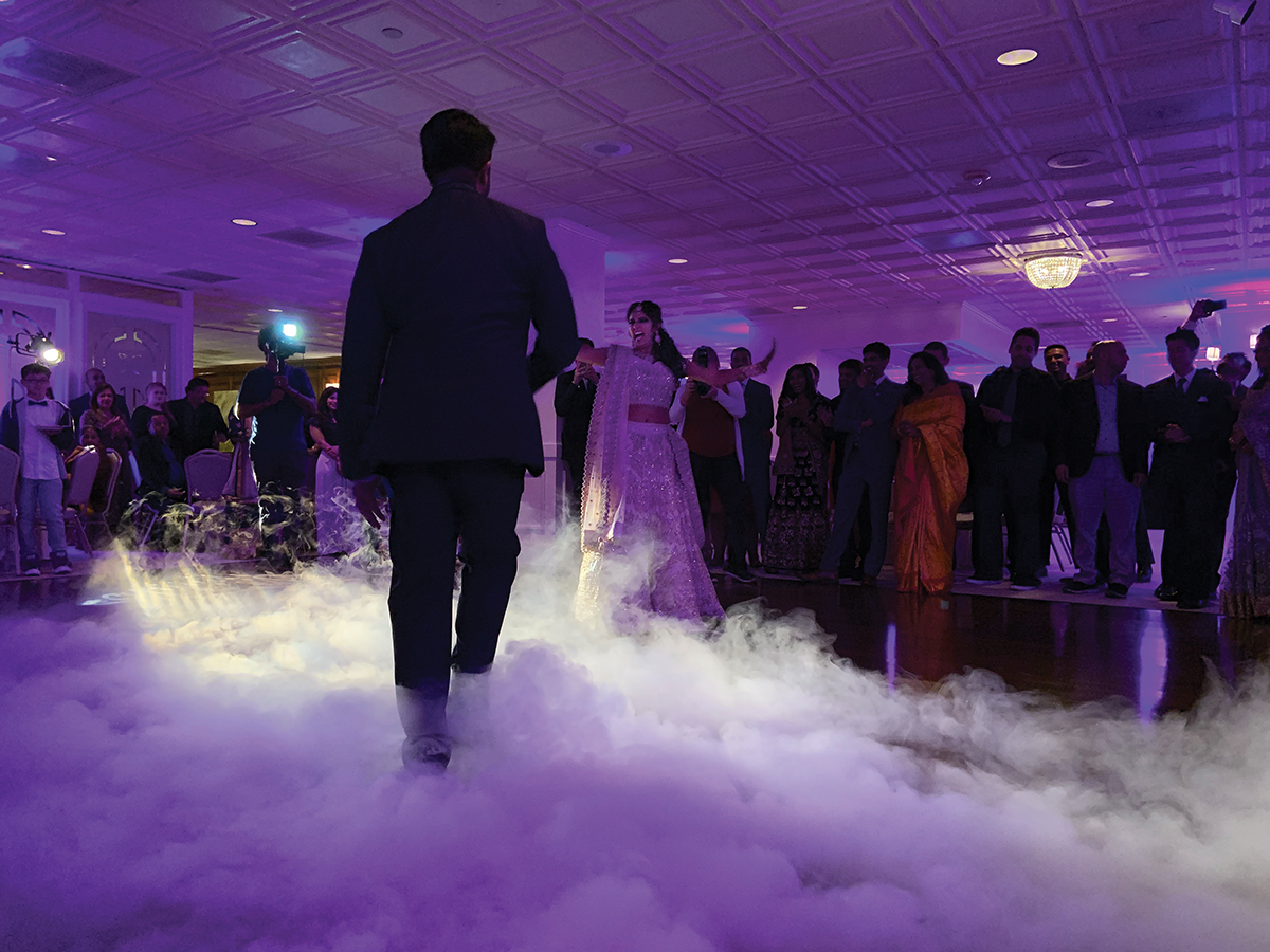 An Indian couple dance on a fog covered dance floor at their wedding reception.