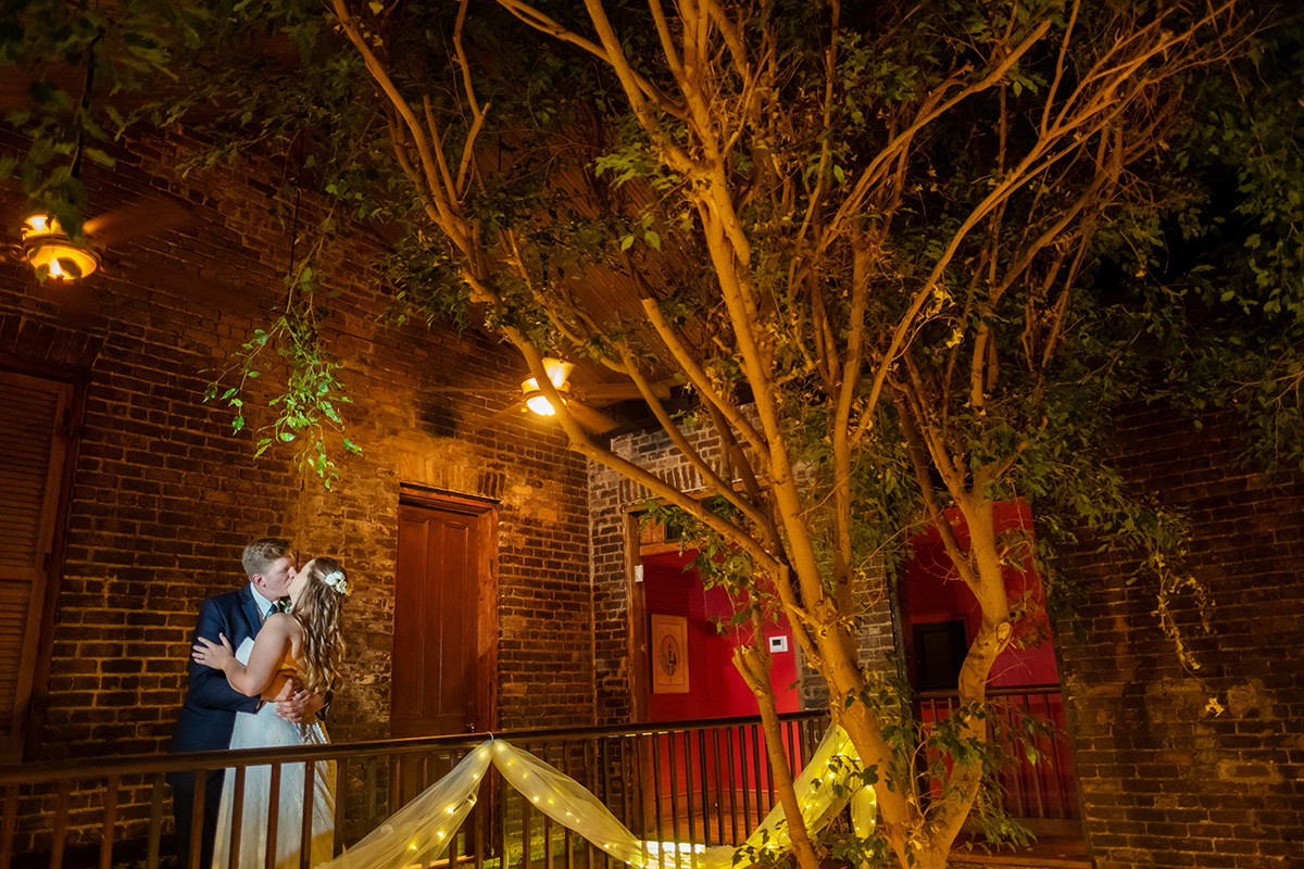 A bride and groom pose on the balcony in Rosy's Jazz Hall atrium. Photo: Studio Tran