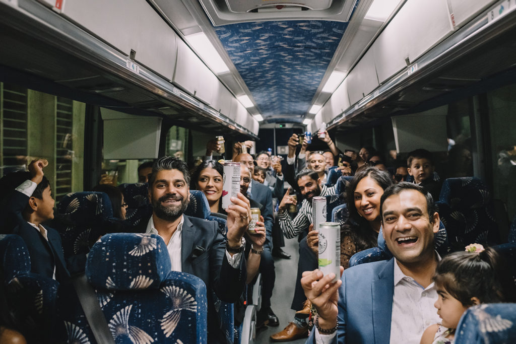 Wedding guests celebrate on a charter bus transporting them to wedding festivities. | photo by Rare Sighting Photography