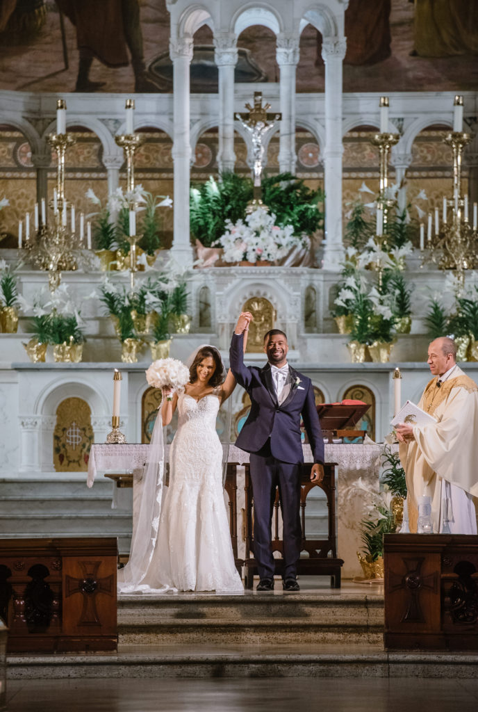 "Newly married couple celebrates their announcement as ""husband and wife"" at their New Orleans wedding ceremony."
