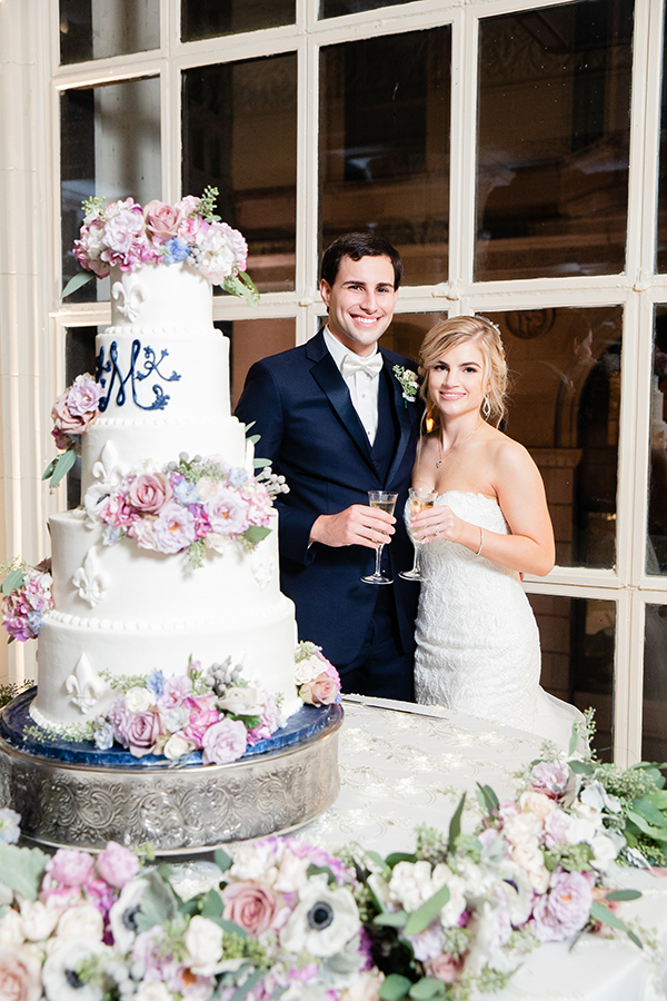 Abbie and Kevin's stunning 5-tier wedding cake by Gambino's Bakery featured a fleur de lis motif and their monogram in royal blue icing. Fresh flowers in soft pastel tones embellished the cake and cake table.