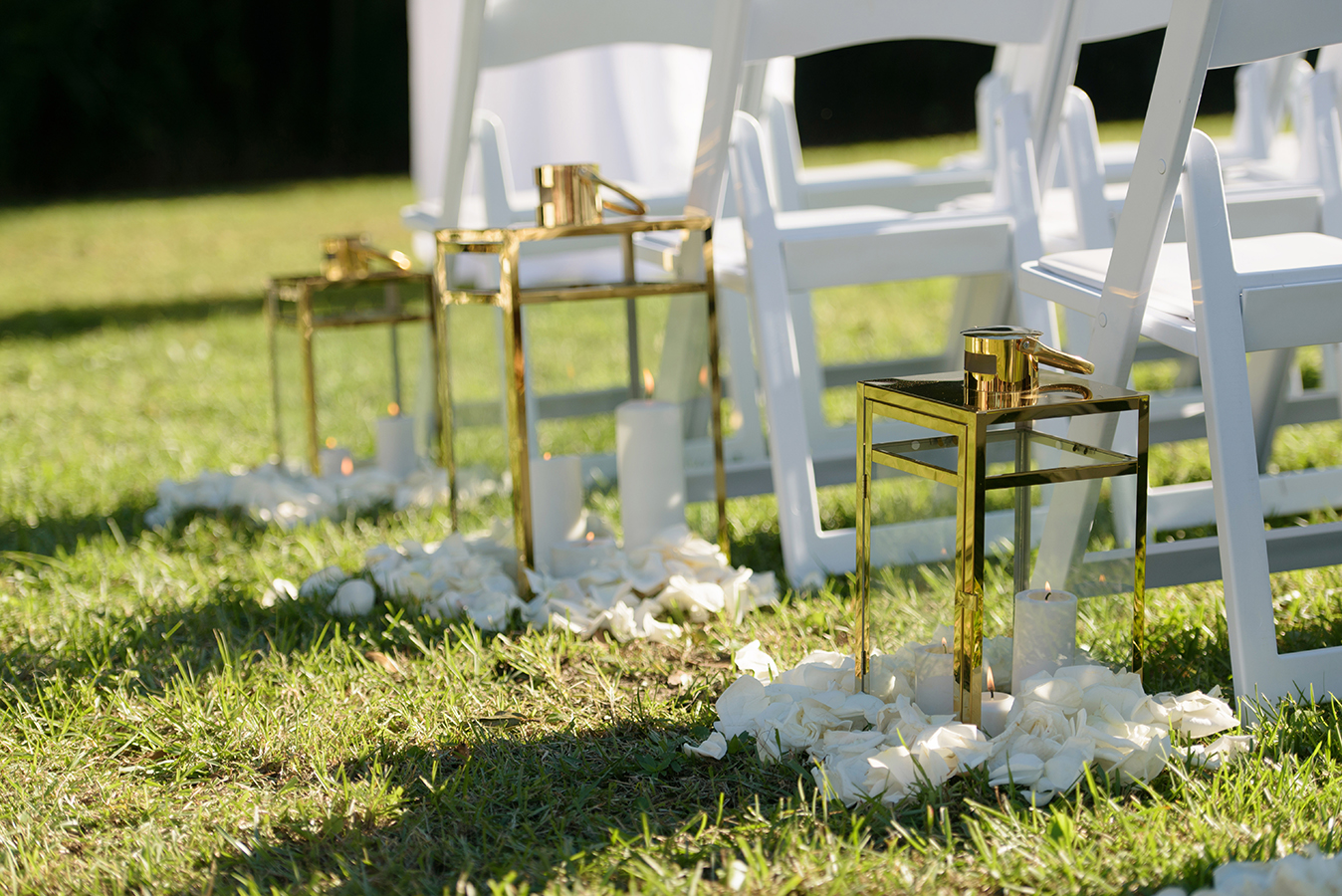 Each aisle was marked with a modern gold lantern set in a bed of ivory rose petals.