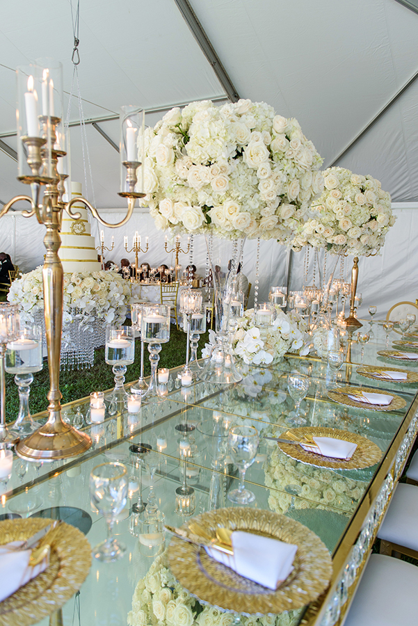 The mirrored bridal party table featured lush floral arrangements and gold candelabra.