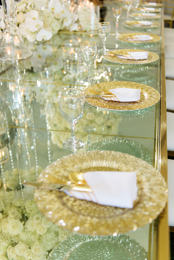 Gold chargers grace each place setting at the bridal party table.