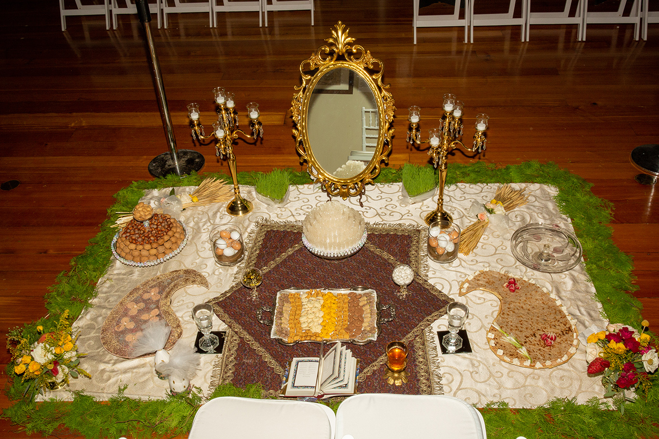 """The """"Sofreh Aghd"""" included Rue Seeds, Traditional Pastries, Mirror and two candelabras, Bread, feta cheese, and greens, Decorated eggs, almonds, walnuts and hazelnuts, Fruits: pomegranates, grapes, apples; Gold Coins; Hafez's Divan, and an Antique Paisley Rug."""