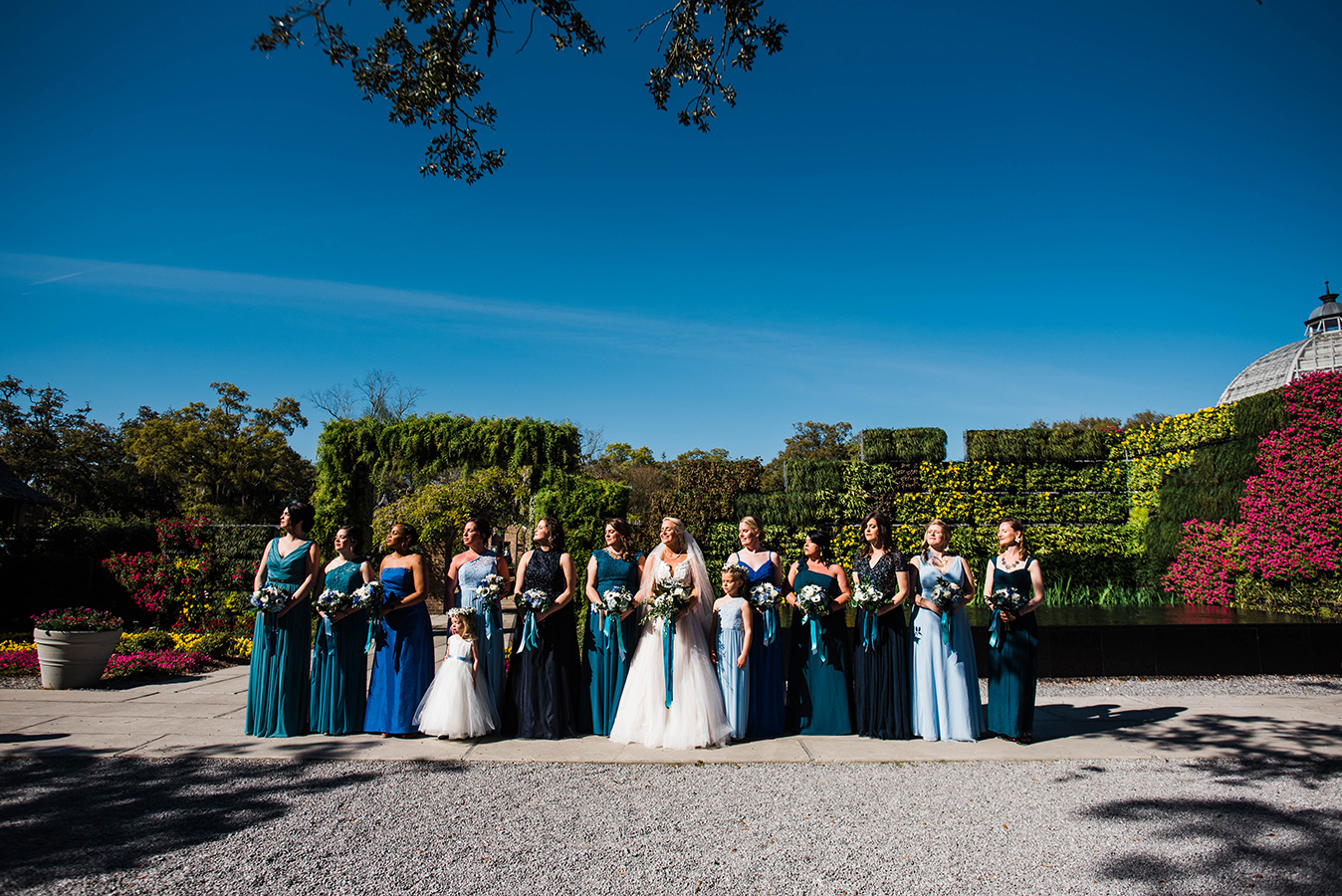 "Kate provided her bridesmaids a teal and blue paint chip color palette and allowed them to each select their own gowns. ""It blended great!"" she shares of the resulting looks."