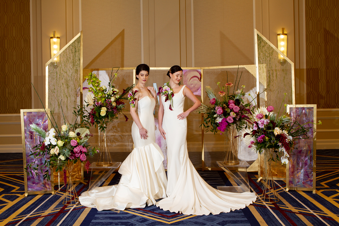 "Julie and Kaylei pose in front of a series of hand-painted screen backdrops amid lush florals from Mitch's Flowers. Both women wear elegant floral pieces, alternatives to traditional bouquets, designed by Mitch's Flowers. A custom-made monogram from Design A Latte Monograms is suspended from the center backdrop panel. Julie's classic strapless Mikado silk gown is from Pearl's Place with a diamond bangle, pearl stud earrings, contour baguette band with pear-shape diamond solitaire ring and an Art Deco studded band from Brilliance in Diamonds. Kaylei is wearing a simple, modern fit-and-flare gown from MaeMe The Bridal Boutique with a diamond bangle bracelet, ""Marigold"" ring and radiant cut diamond studs from Brilliance in Diamonds."