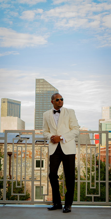 Jarrel is wearing a classic shawl lapel ivory dinner jacket ensemble with a Jack Mason Nautical Chronograph watch, Randolph Aviator Sunglasses and gold crown cufflinks from John's Tuxedos and a gray and rose gold band from Brilliance in Diamonds.