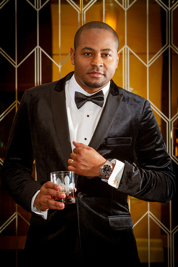 Jarrel is wearing a black velvet peak lapel tuxedo jacket, Jack Mason Diver 42mm watch, and gold Fleur De Lis cufflinks from John's Tuxedos and a gunmetal tungsten wedding band from Brilliance in Diamonds.