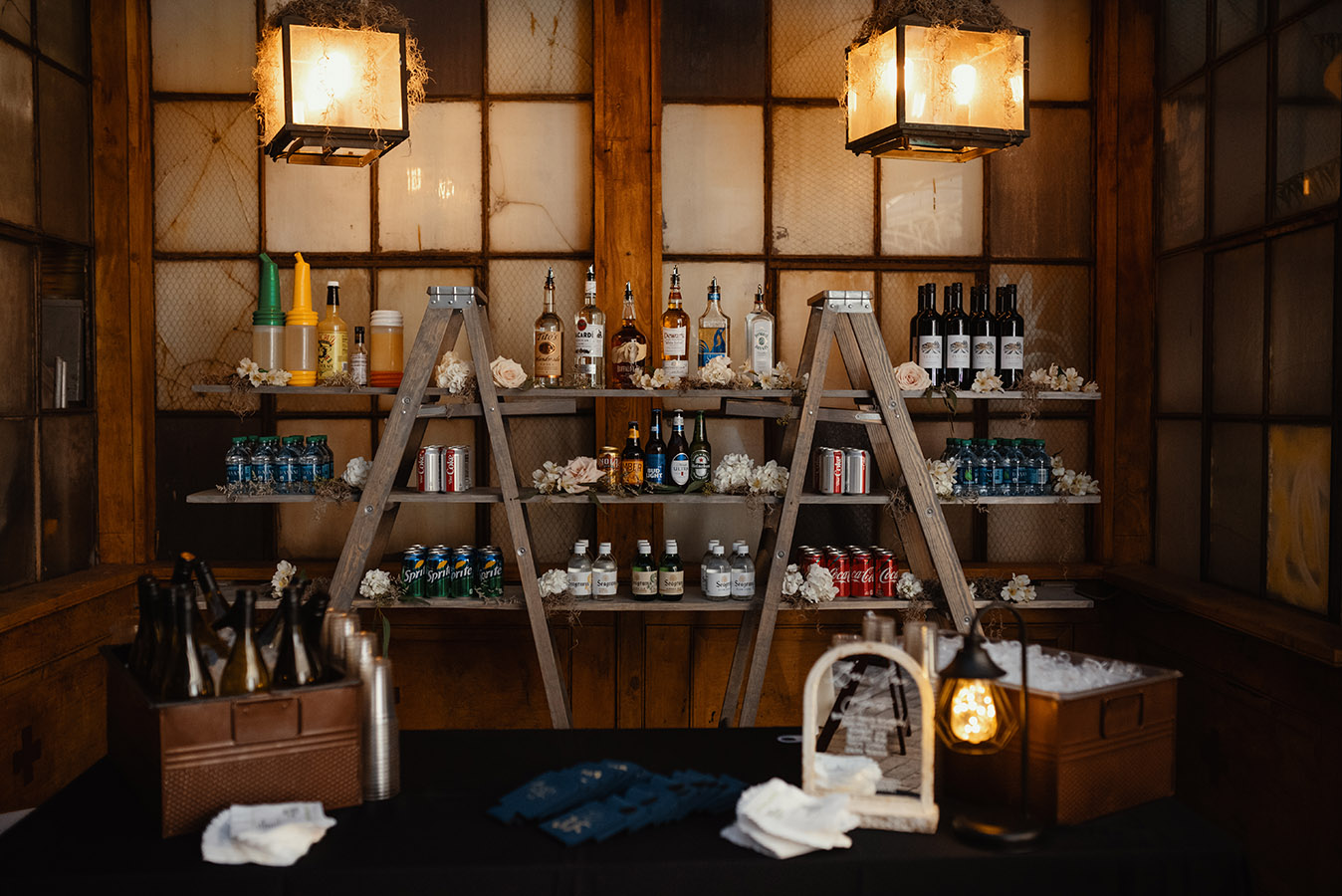 The ladder shelf bar back was custom created for Jeanne and Dan's wedding by True Value Rental. Abita and NOLA Blonde beers were displayed in a pirogue. Photo by Dark Roux