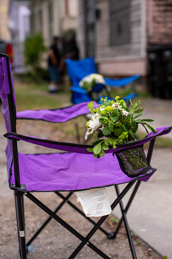 Parade chairs with flowers, placed six feet apart on the sidewalk, serve as seating for the wedding guests.