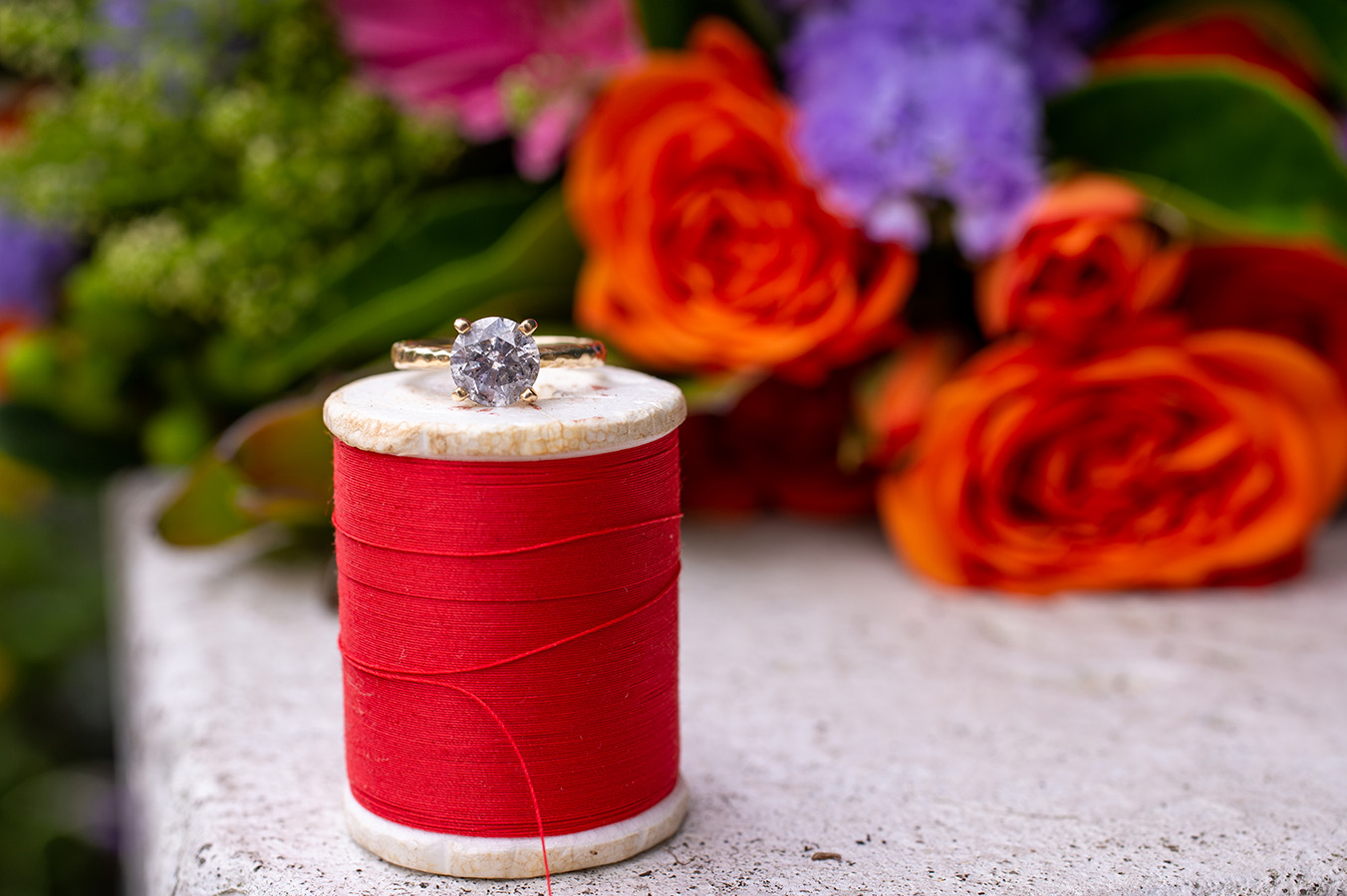 """""""We hadn't ordered our wedding rings yet,"""" says Elizabeth, so she had to think outside of the box. """"I was kind of thinking along the lines of those Celtic ceremonies where they bind hands, but I had no ribbon or rope. I had the idea right before the wedding when I was flipping through Diane's wedding itinerary, saw the """"ring exchange"""", and was literally like """"aw crap! That's kind of a big part of all of this."""" I went through my grandmother's sewing kit, grabbed the prettiest red thread, then handed it off to Marianne for pictures with my engagement ring while mumbling, """"with this string, I thee wed,"""" followed by maniacal laughter."""""""