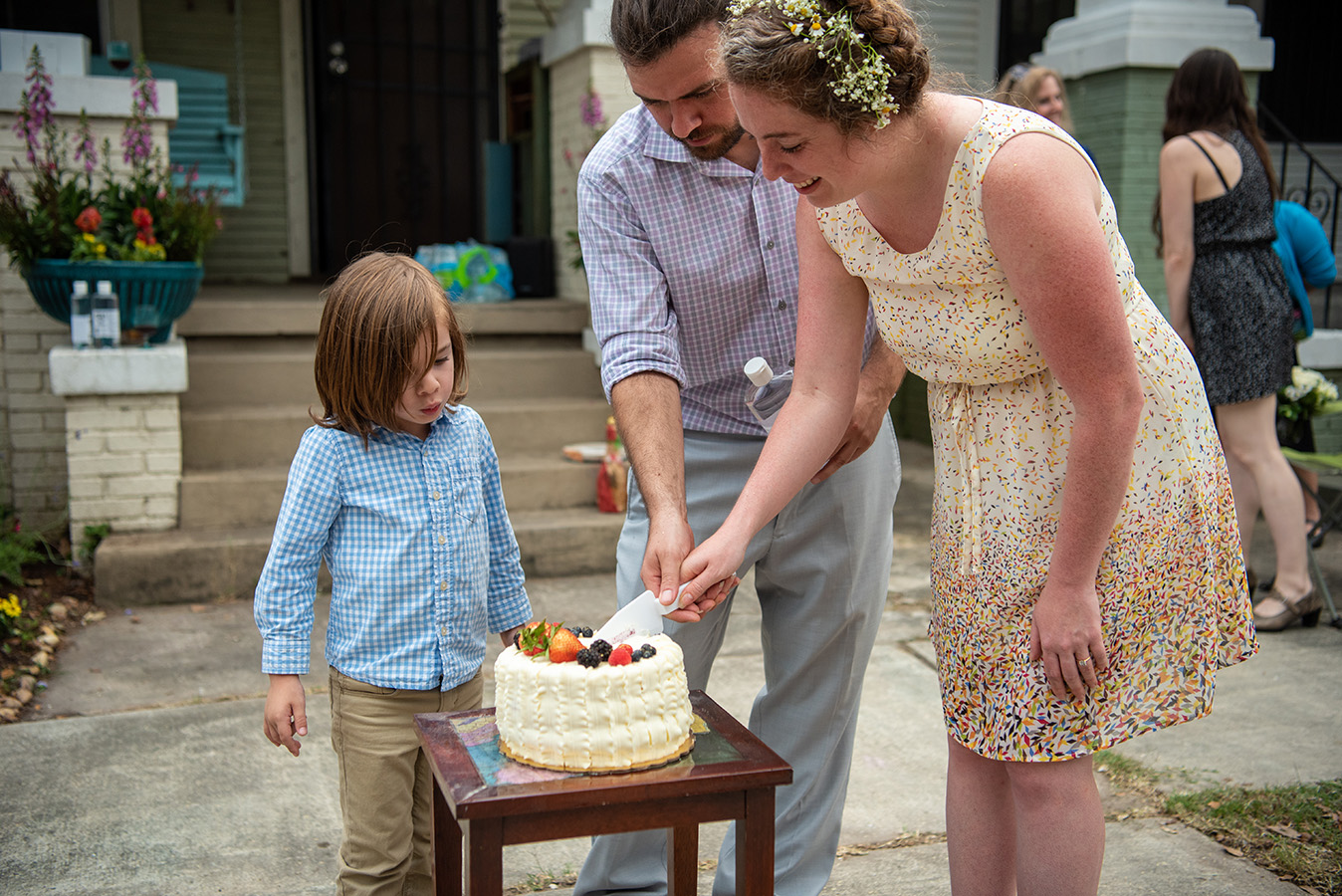 Elizabeth and Greg cut their Berry Chantilly wedding cake from Bywater Bakery with their son Frank watching.