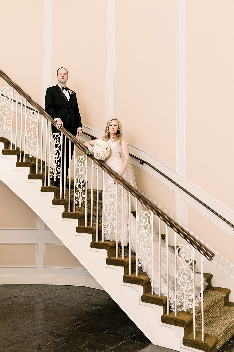 A bride and groom pose on the double circular staircase at Chateau. Photo: Theresa Elizabeth Photography