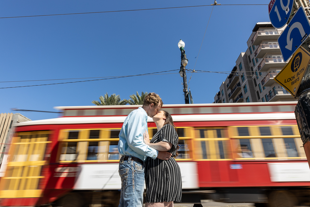 An couple kisses on Canal Street with the streetcar in the background. | Photos by Amin Russell Photography