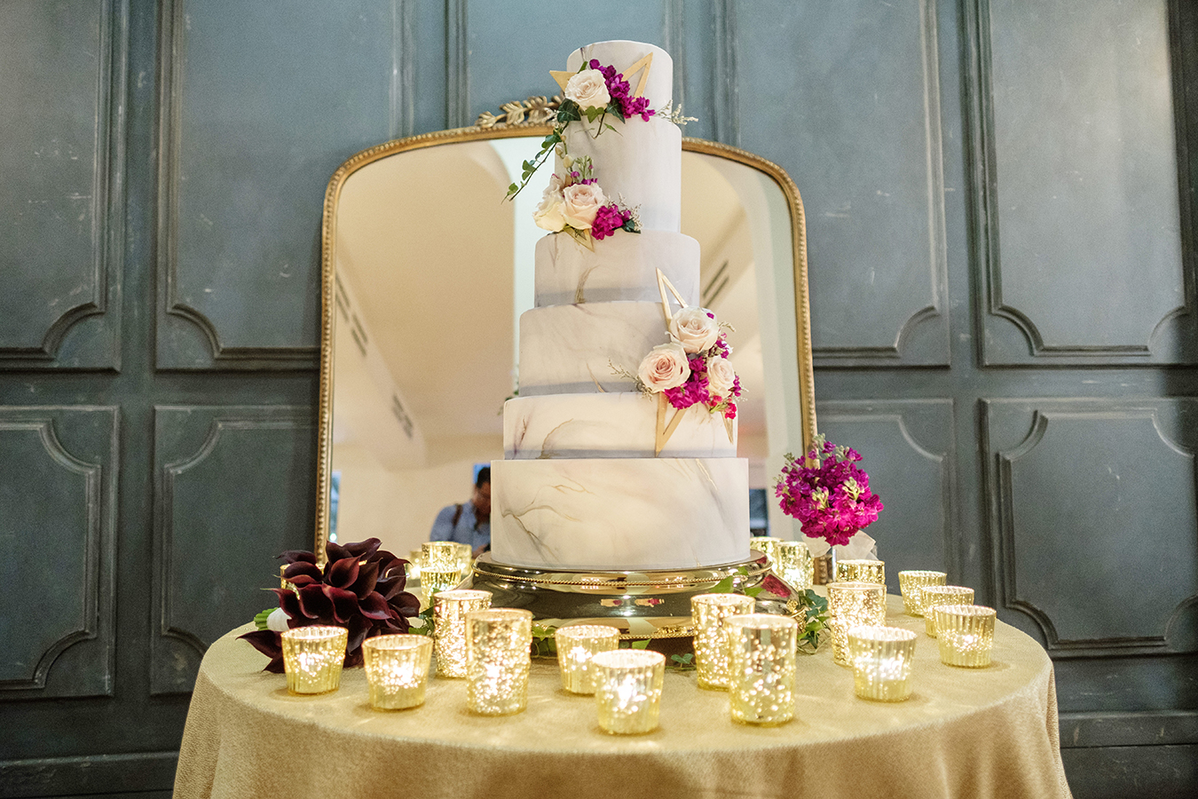 The wedding cake, designed by Chasing Wang, featured six tiers covered with marbled fondant and accented with fresh flowers and geometric decorations.