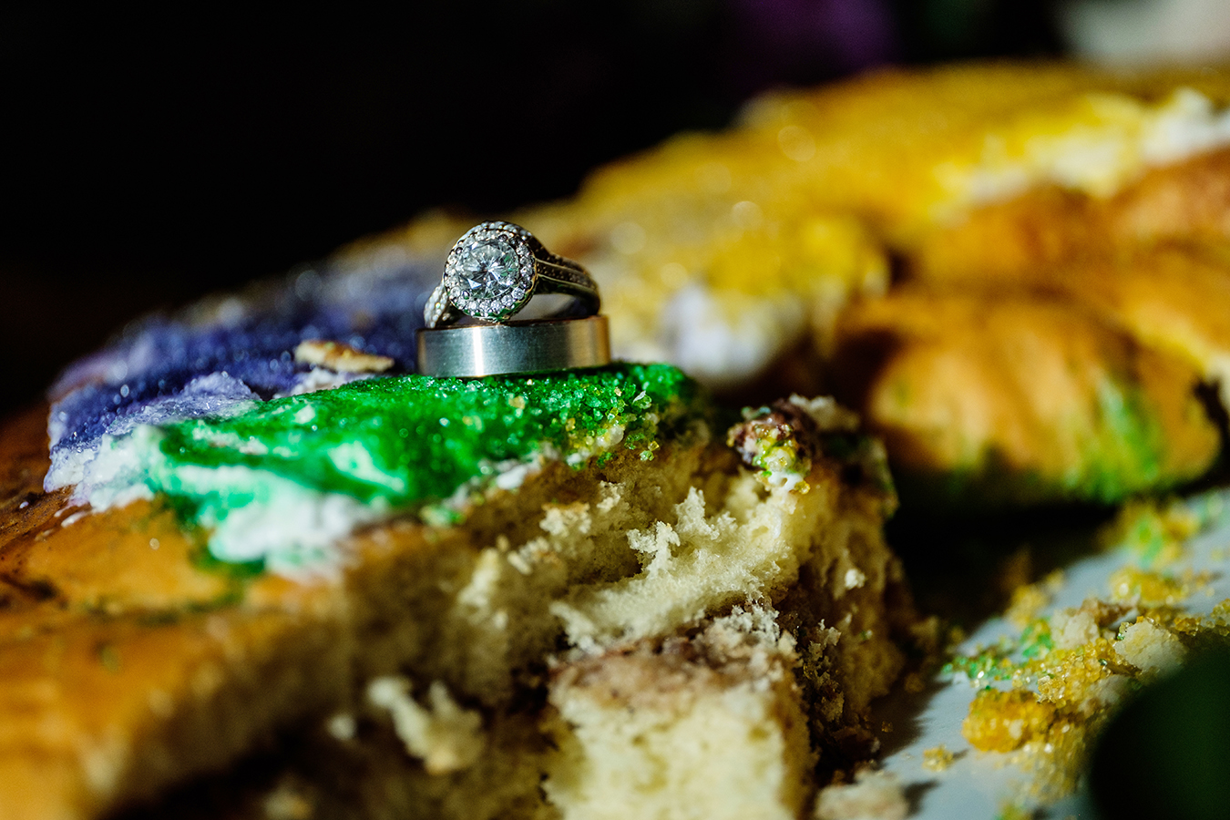 Alex and Greg's wedding rings on a slice of king cake