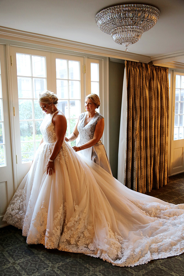 After helping so many other brides find the perfect dress, Courtney's mother, Linda, helps her daughter into her own wedding gown.