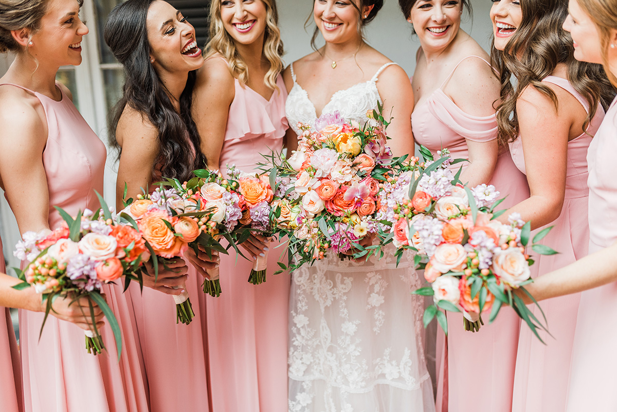 Bride with bridesmaids in coral dresses with colorful bouquets. Gabby Chapin Photography