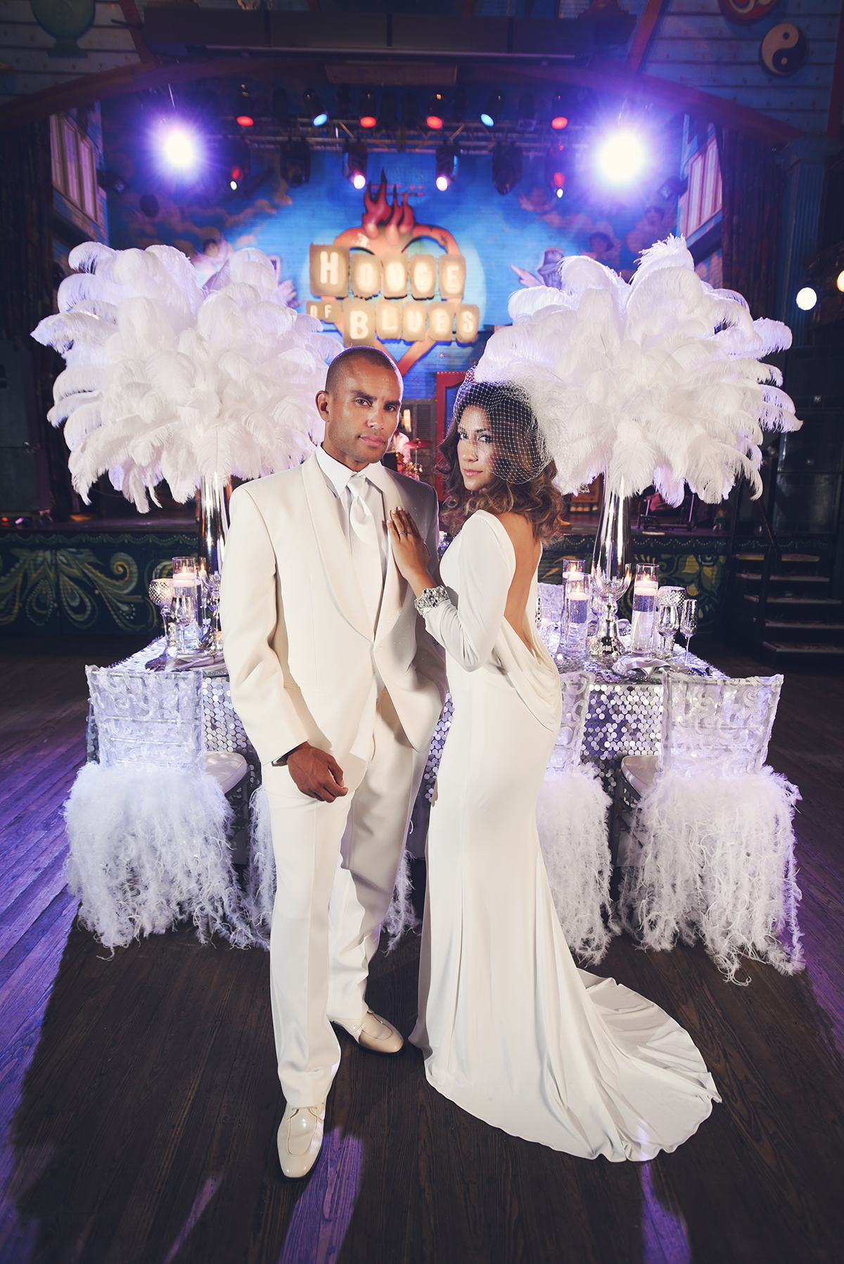 Sexy and chic, Fabiola stuns in a sleek, low-back ivory jersey bridal gown with rhinestone banding at the wrists. Charles' all-white ensemble from John's Tuxedos is perfect for the hot summer nights in New Orleans.