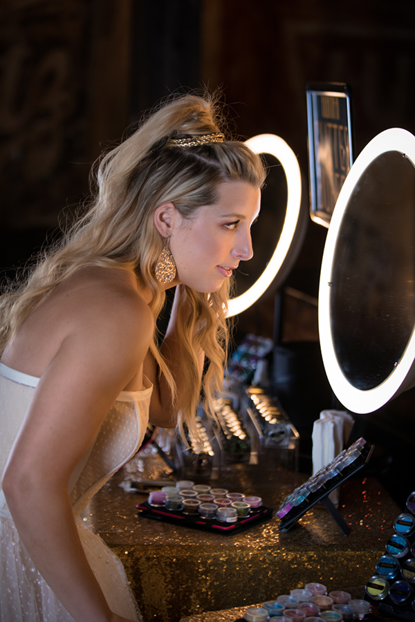 A bride checks out her Glitter Bar glitter makeup in a lighted mirror. Photo: Brian Jarreau