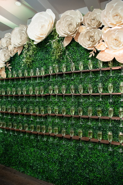 Nola Grace Decor's champagne hedge wall with paper flowers. Photo: Brocato Photography Collective