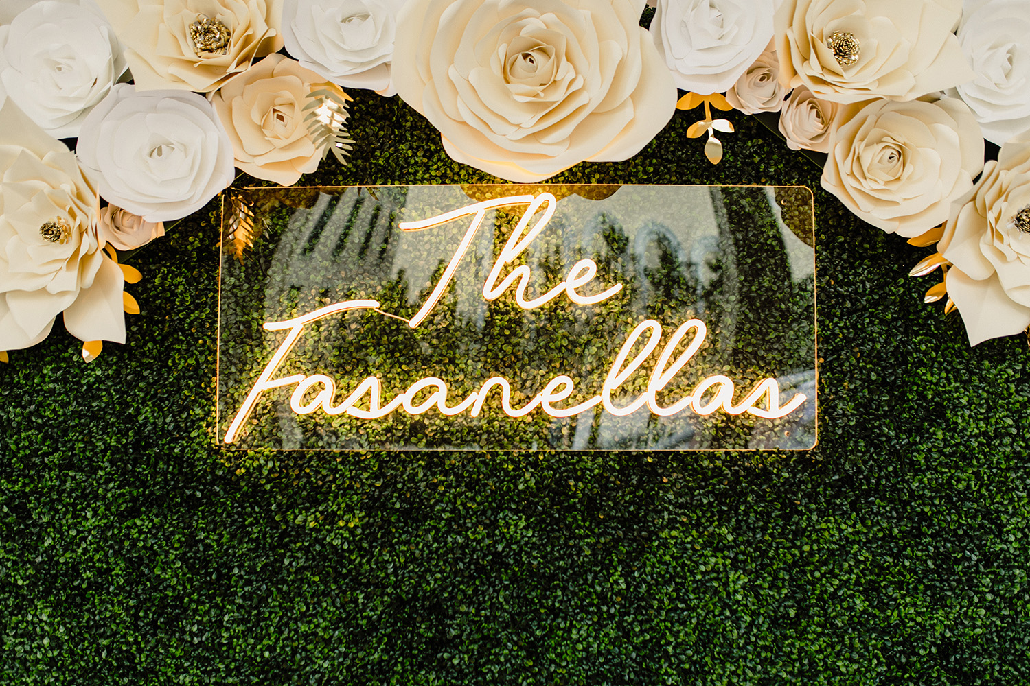 Nola Grace Decor's hedge wall photo opp with paper flowers and neon sign. Photo by Kristen Soileau.