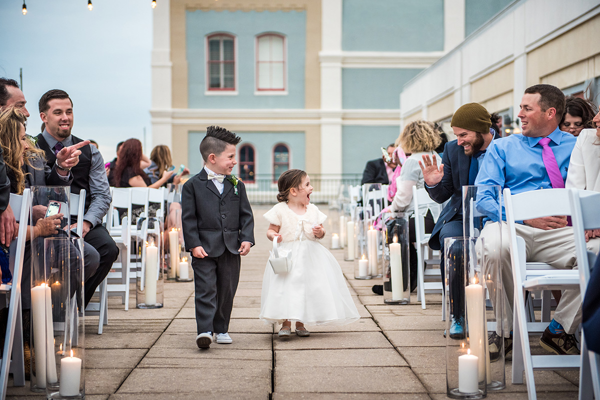 Ringbearer and flowergirl walk down the aisle at a Riverview Room wedding ceremony. Photo by The Red M Studio
