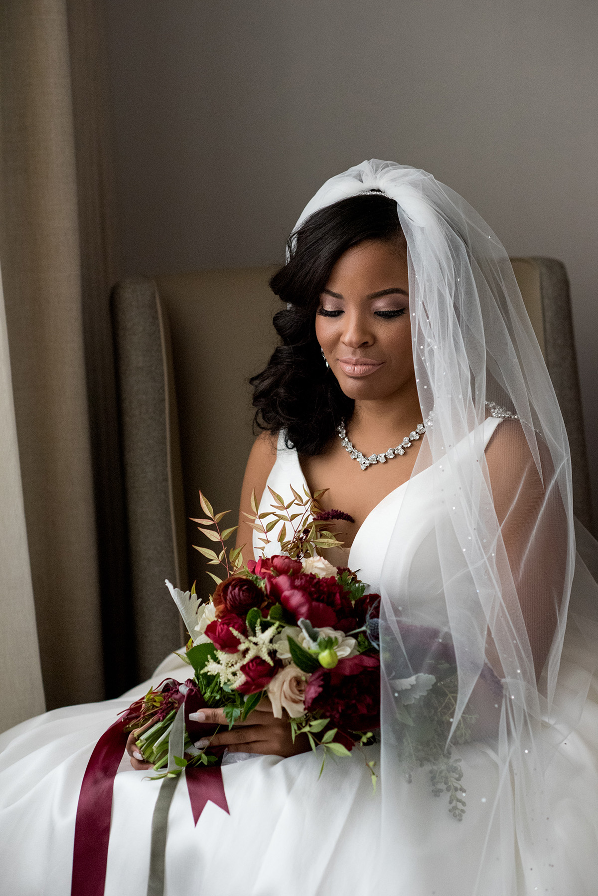 Portrait of a bride with a red bouquet. Photo by The Red M Studio