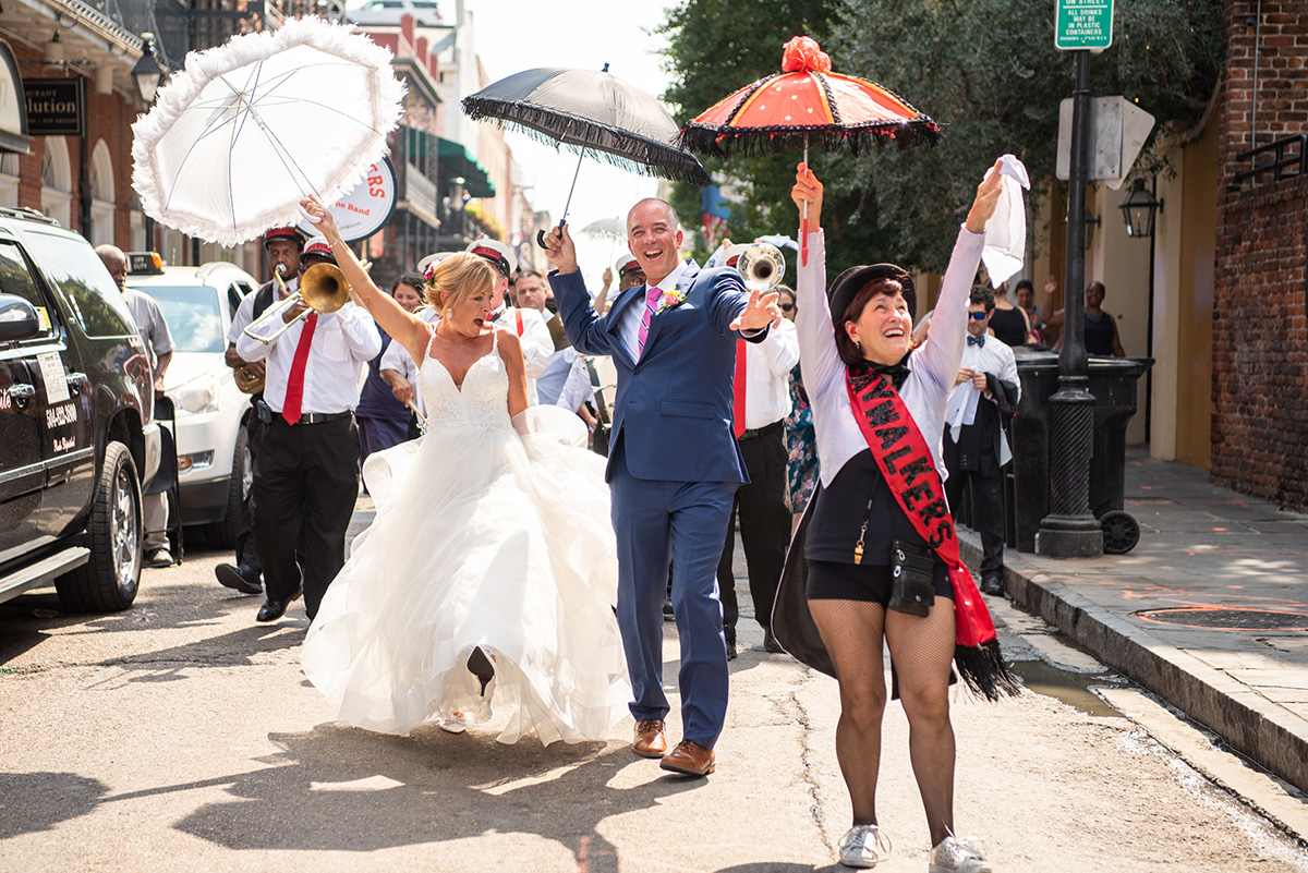 A wedding party second lines thru the French Quarter in New Orleans. Photo by The Red M Studio