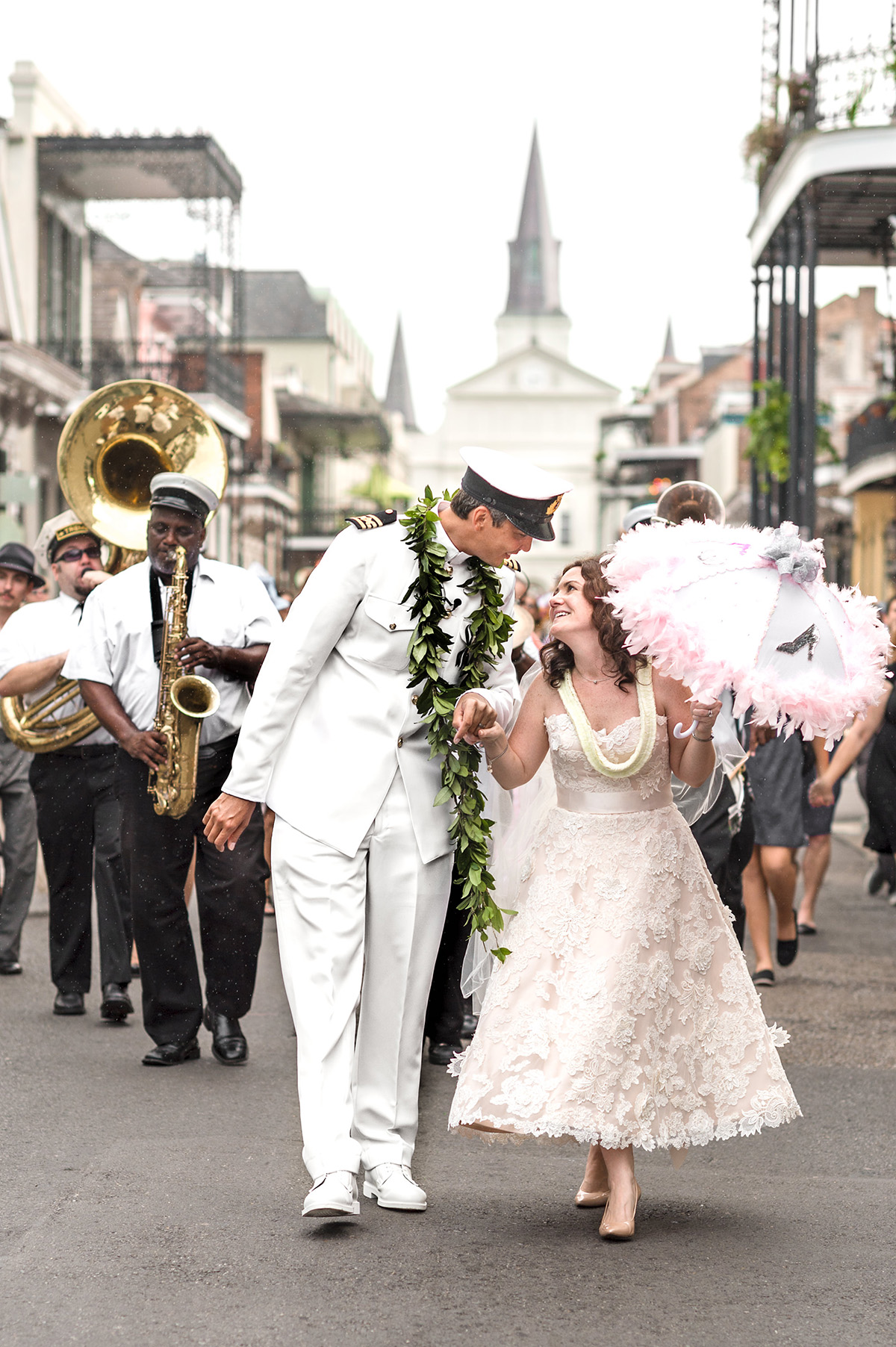 A bride and groom second line through the French Quarter with St. Louis Cathedral in the background. Photo by The Red M Studio