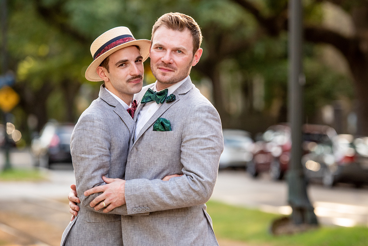 Grooms pose for a photo on St. Charles Ave in New Orleans on their wedding day. Photo by The Red M Studio